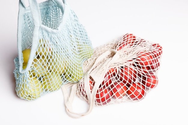 Bio-äpfel in weidentasche zum einkaufen auf weißem hintergrund, öko-einkaufstasche-konzept. zero-waste-konzept mit kopienraum, plastikfreies konzept