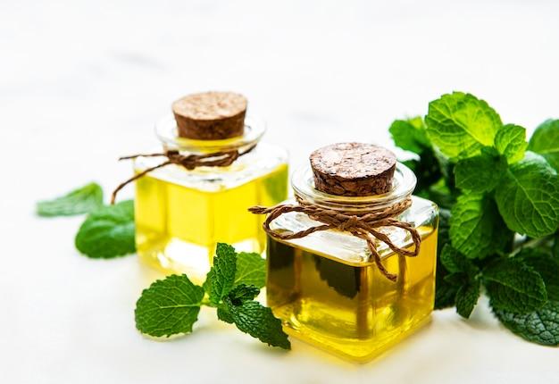 Bio ätherisches minzöl mit grünen blättern auf einem weißen
