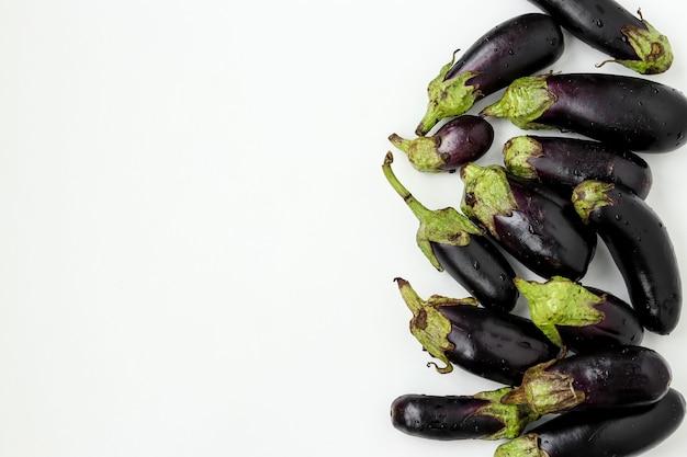 Bio-auberginen auf weißem hintergrund, bio-gemüse-konzept, horizontale ausrichtung, kopierraum, draufsicht top