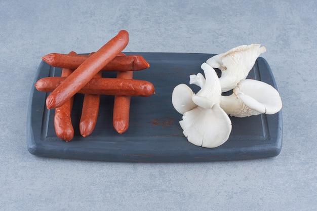 Bio-austernpilz und salami auf holzbrett.