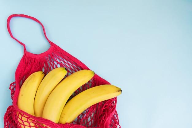 Bio-banane in netzstringtasche. flachgelegt, draufsicht. null abfall, plastikfreies konzept. gesunde, saubere ernährung und entgiftung