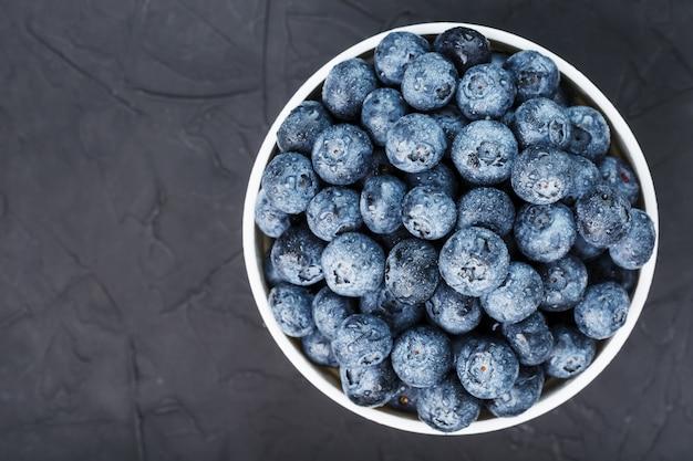 Bio-blaubeeren in einer weißen tasse auf einem schwarzen brett