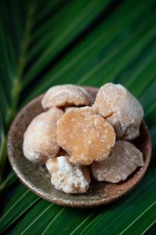 Bio-brauner palmzucker oder kokosnusszucker aus kokosnusssaft mit grünen kokosnussblättern.