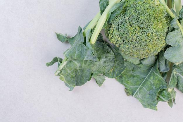 Bio-brokkoli mit blättern auf weißer oberfläche