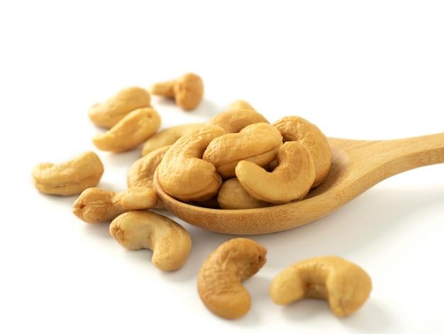 Bio-cashewnüsse in holzlöffel und haufen mandeln isoliert auf weiß