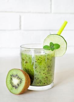Bio-cocktail mit minze, limette und kiwi im glas.