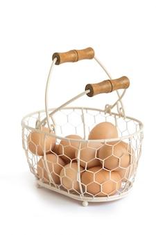 Bio-eier in rustikalem drahtkorb provence im weißen hintergrund
