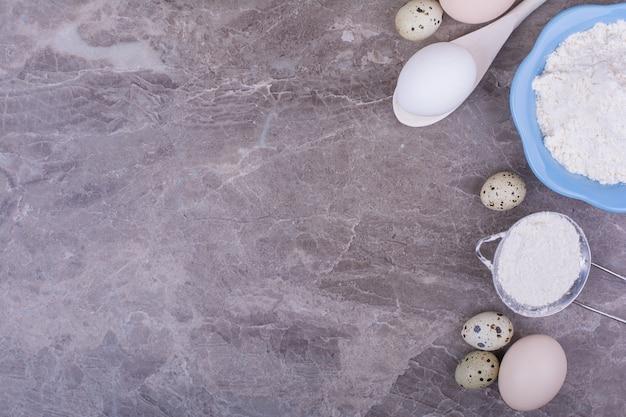 Bio-eier mit einer tasse mehl auf dem stein