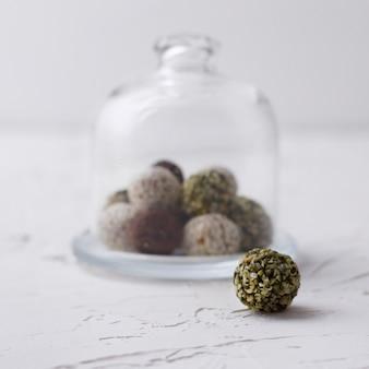 Bio-energiebissen mit datteln, kürbiskernen, mandeln, walnüssen und sesam im glasbehälter.