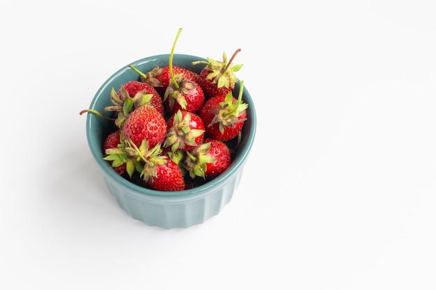 Bio-erdbeeren in der grünen schüssel auf weißem hintergrund. sommerkomposition