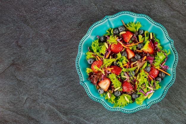 Bio-erdbeersalat mit salat, kohl und karotten