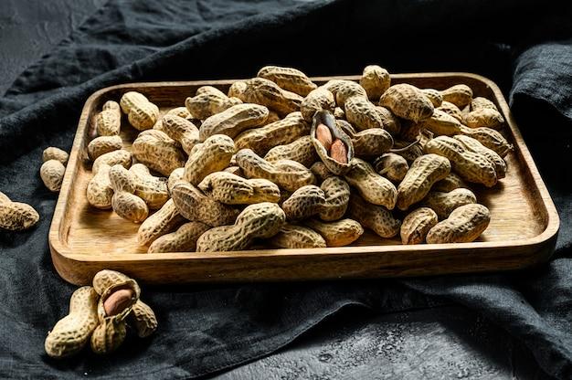 Bio-erdnüsse. die rohe erdnuss in der schale. schwarzer hintergrund. draufsicht