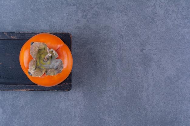Bio-frische kaki-früchte an bord, auf der dunklen oberfläche