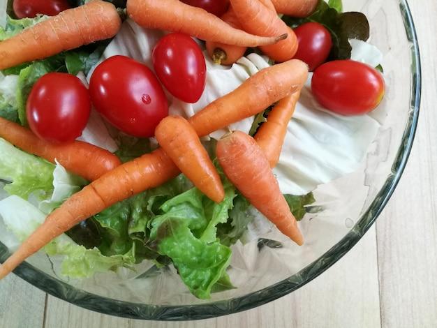 Bio-frischer salat auf glasschüssel. tomaten-, karotten- und salatmenü für eine gesunde ernährung.
