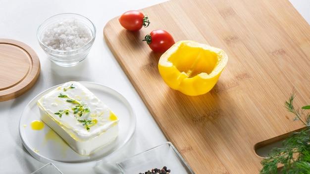 Bio gelbe paprika, tomaten auf einem holzbrett, dill, käse und salz auf einem weißen holztisch. frische zutaten, schritt für schritt kochen diät-salat.