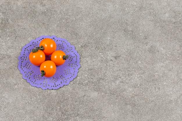 Bio gelbe tomaten auf grau.