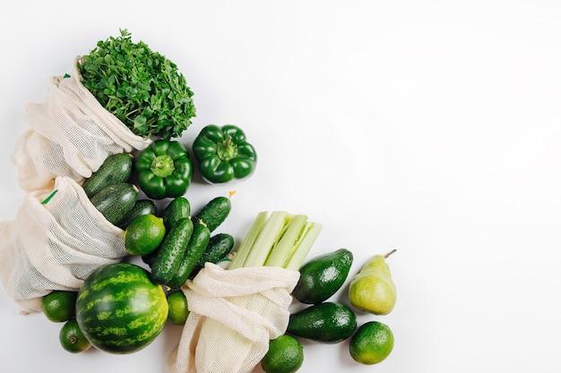 Bio-gemüse und frisches grün in mehrwegbeuteln. nachhaltiger lebensstil. zero-waste-shopping-konzept. flache lage, ansicht von oben