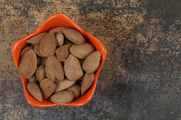 Bio geschälte mandeln in orangenschale.