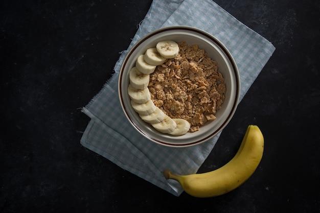 Bio gesunder haferbrei mit frischen bananen. die weiße porzellanschale mit serviette unter der schale.
