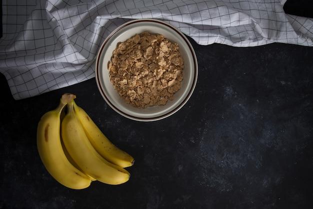 Bio gesunder haferbrei mit frischen bananen. die weiße porzellanschale mit serviette