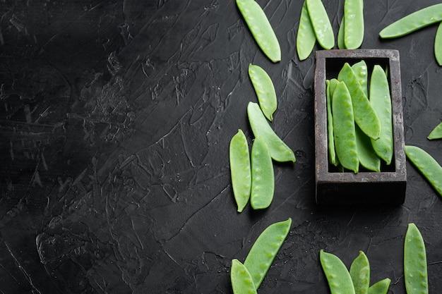 Bio green sugar snap peas ready to eat set, in holzkiste, auf schwarzem steintisch