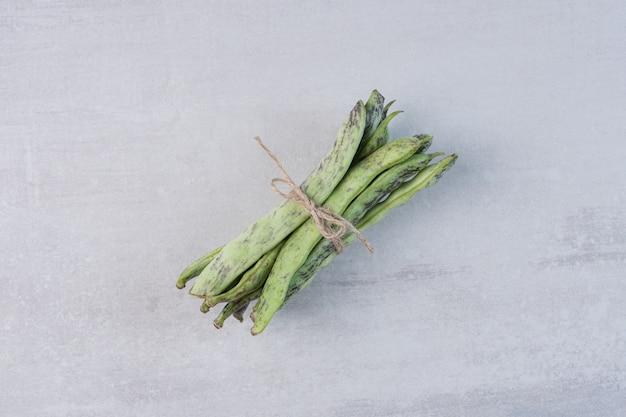 Bio grüne bohnen mit seil auf steinoberfläche gebunden. hochwertiges foto