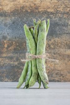 Bio grüne bohnen mit seil auf steintisch gebunden. hochwertiges foto