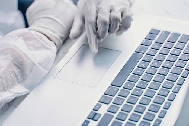 Bio hazard mann mit laptop. geschäftsmann, der an laptop-computer in quarantäne arbeitet.