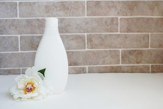 Bio-körperlotion und frische weiße blume im bad