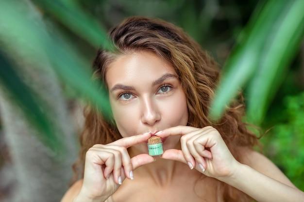 Bio-kosmetik. hübsche junge frau, die glas mit lidschatten hält