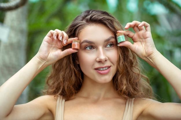 Bio-kosmetik. junge frau, die gläser mit lidschatten in ihren händen hält