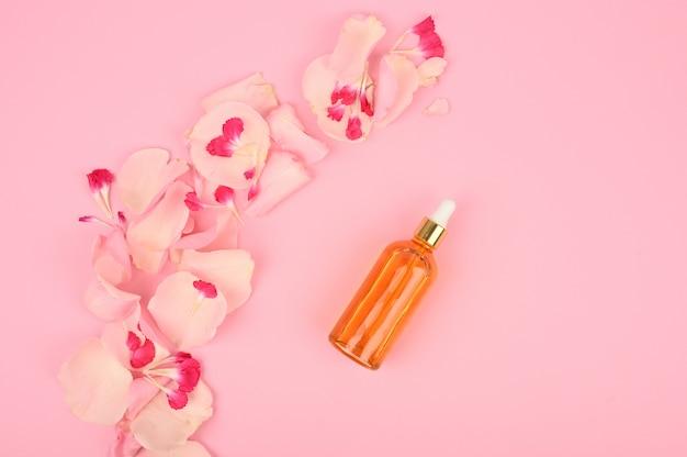 Bio-kosmetik mit rosenöl auf rosa raum. draufsicht.