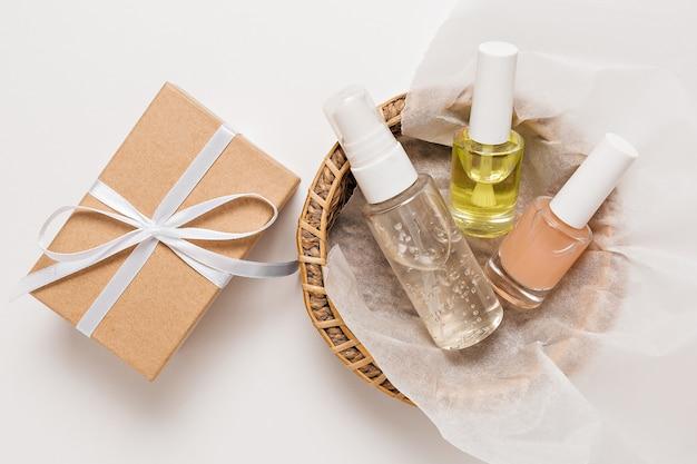 Bio-kosmetik und geschenke für den urlaub. flache lage, klare glaspumpflasche mit draufsicht, bürstenglas, feuchtigkeitsspendendes serumglas in einem papierkorb auf weißem hintergrund. naturkosmetik spa