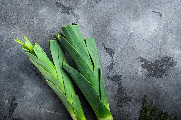 Bio-lauchzwiebelstiele mit kräuterzutaten zum kochen von geschmortem lauch, auf grauer strukturierter hintergrundoberansicht mit raum für text.