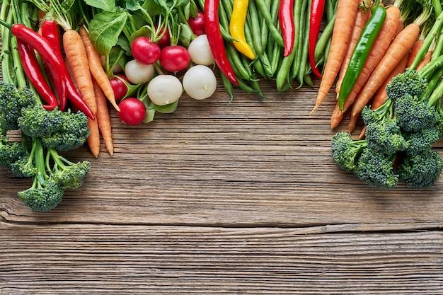 Bio-lebensmittel. brokkoli, grüne bohnen, rettich, karotten und bunter paprikapfeffer auf rustikalem hölzernem hintergrund. draufsicht, kopie, raum.