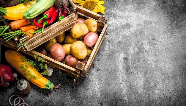 Bio-lebensmittel frische ernte von gemüse in einer alten box auf einem rustikalen hintergrund