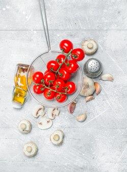 Bio-lebensmittel. frische tomaten mit pilzen und gewürzen. auf einer rustikalen oberfläche.