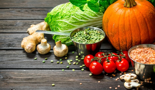 Bio-lebensmittel. frisches gemüse und gewürze mit hülsenfrüchten auf holztisch.