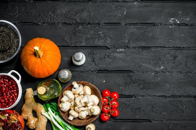 Bio-lebensmittel. gesundes gemüse und pilze mit bohnengetreide. auf einem schwarzen rustikalen tisch.