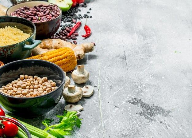 Bio-lebensmittel. gesundes sortiment an obst und gemüse mit hülsenfrüchten. auf einem rustikalen tisch.