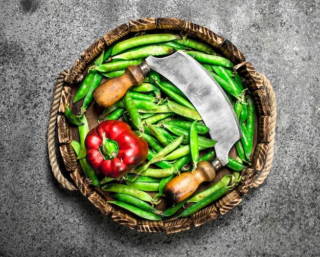 Bio-lebensmittel grüne erbsen mit paprika und einem alten messer auf einem tablett auf einem rustikalen hintergrund