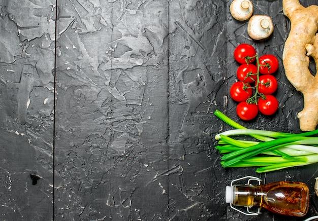 Bio-lebensmittel. reife tomaten mit pilzen und olivenöl auf schwarzem rustikalem tisch.