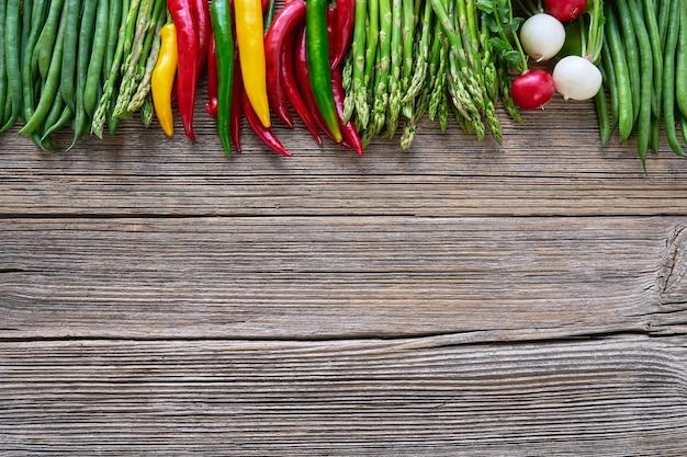 Bio-lebensmittel. spargel, grüne bohnen und bunter pfeffer der scharfen paprikas auf rustikalem hölzernem hintergrund.
