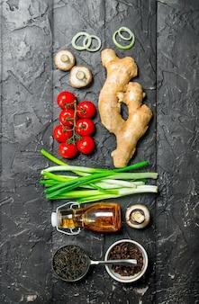 Bio-lebensmittel. verschiedene gemüsesorten mit wildreis auf schwarzem rustikalem tisch.