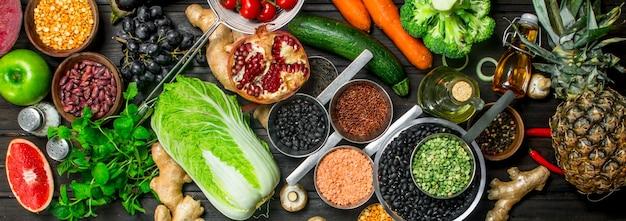 Bio-lebensmittel. vielzahl von gesundem obst und gemüse mit hülsenfrüchten auf rustikalem tisch.