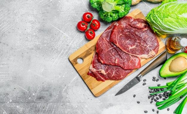 Bio-lebensmittel. vielzahl von gesunden lebensmitteln mit rindersteaks auf rustikalem tisch.
