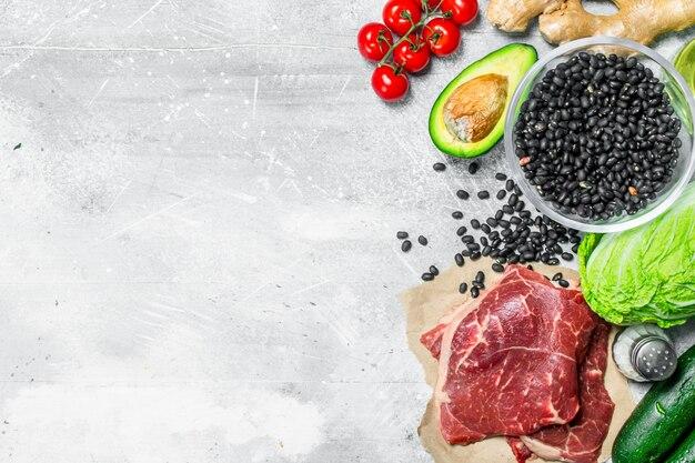 Bio-lebensmittel. vielzahl von gesunden lebensmitteln mit rohem rindfleisch auf rustikalem tisch.