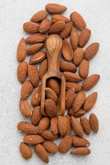 Bio mandelnüsse und holzlöffel flach liegen