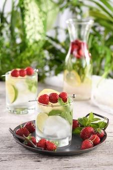 Bio-mojito-cocktail mit frischem limetten-weiß-rum kombiniert mit frischer erdbeere und minze