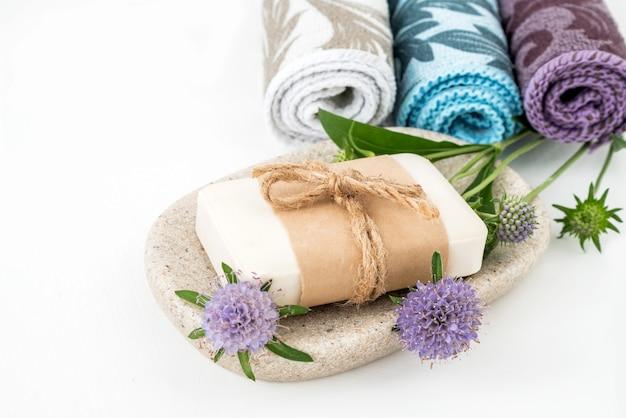 Bio-naturseife auf tablett mit aromatischen pflanzen mit gerollten bunten handtüchern im hintergrund